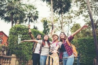 Groupe d'amis heureux leva la main sur le fond de la ville.