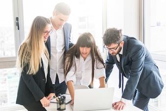 Groupe de gens d'affaires à la recherche d'un ordinateur portable au bureau