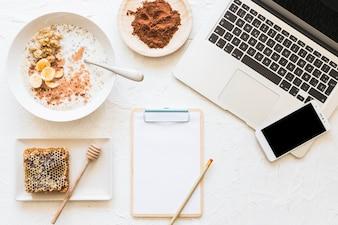 Gruau et nid d'abeilles trempés avec ordinateur portable et téléphone portable sur le lieu de travail