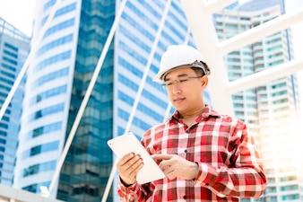 Guy exécutif ingénieur utilise une tablette pour enregistrer son travail ou son calendrier pour lui rappeler plus tard