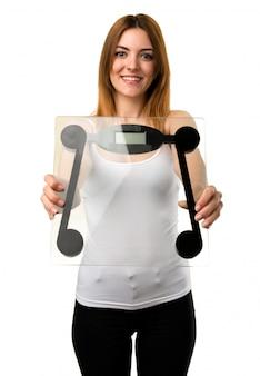 Heureuse belle jeune fille avec un appareil de pesage