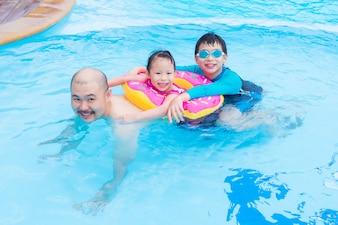 Heureuse famille asiatique jouant ensemble dans la piscine