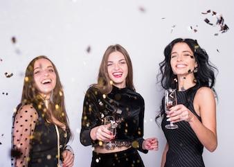 Heureuse femme debout avec des coupes à Champagne sous les paillettes