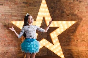 Heureuse jeune fille jouant devant une étoile brillante contre le mur de briques