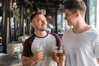 Heureux amis tenant des verres de bière