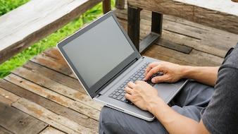 Homme à l'aide d'un ordinateur portable sur le balcon