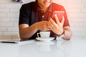 Homme à l'aide d'un téléphone intelligent dans un café