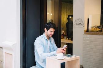 Homme à l'aide de téléphone portable au café