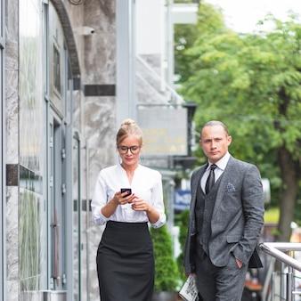 Homme affaires, debout, femme, utilisation, téléphone portable