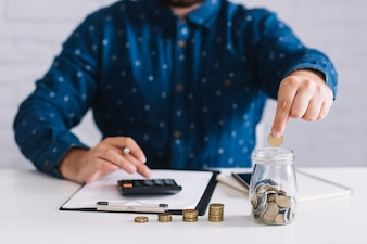 Homme affaires, mettre, pièces monnaie, dans, pot, utilisation, calculatrice, sur, lieu de travail