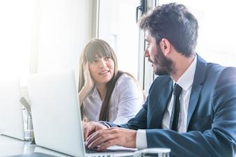 Homme affaires, regarder, jeune femme souriante, utilisation, ordinateur portable
