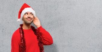 Homme avec des vêtements rouges célébrant les vacances de Noël à l'écoute de quelque chose