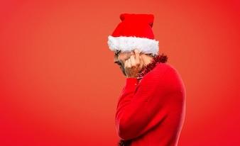 Homme avec des vêtements rouges célébrant les vacances de Noël couvrant les deux oreilles avec les mains