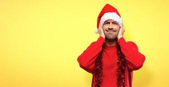 Homme avec des vêtements rouges célébrant les vacances de Noël couvrant les deux oreilles