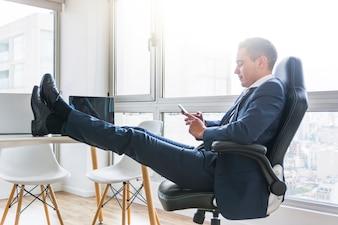 Homme d'affaires à l'aide de téléphone portable assis sur un fauteuil avec sa jambe croisée sur la table