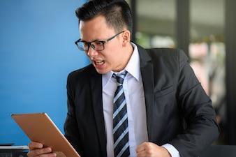 Homme d'affaires asiatique en colère regarder tablette et avoir le sentiment déçu