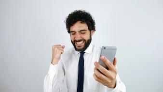 Homme d'affaires avec un téléphone portable à la main célébrant de bonnes nouvelles