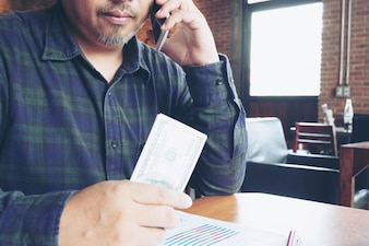 Homme d'affaires parlant sur téléphone portable et tenant le dollar en main