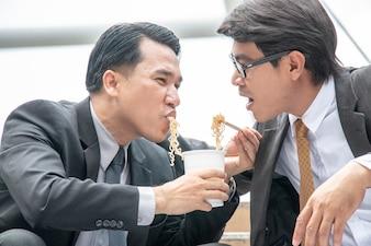 Homme d'affaires partage une nouille instantanée pendant l'heure du déjeuner