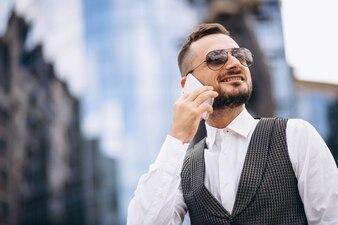 Homme d'affaires réussi par le gratte-ciel parlant au téléphone