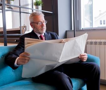 Homme d'affaires senior assis sur un canapé en lisant un journal au bureau