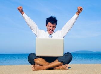 Homme d'affaires sur la plage avec un ordinateur portable