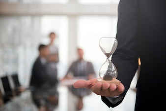 Homme d'affaires tenant un sablier, signifiant l'importance d'être à l'heure