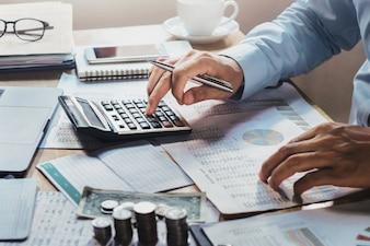 Homme d'affaires travaillant sur le bureau dans le bureau à l'aide de la calculatrice