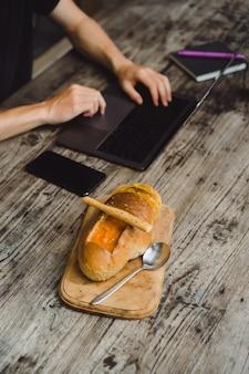 Homme dans un café travaillant avec un ordinateur portable, manger, travailler, smartphone