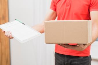 Homme de livraison de cultures avec boîte et presse-papiers