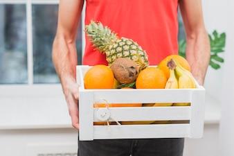 Homme de livraison de cultures avec des fruits