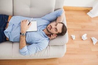 Homme décontracté couché sur un canapé avec des papiers froissés