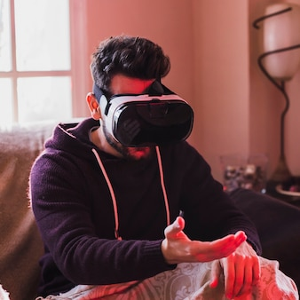 Homme en lunettes de VR en regardant la main