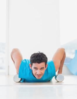 Homme faisant des push ups avec des haltères dans un studio de fitness