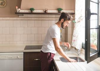 Homme lavant la vaisselle dans la cuisine