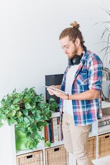 Homme moderne avec tablette à la maison