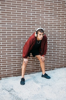 Homme sportif devant le mur de briques