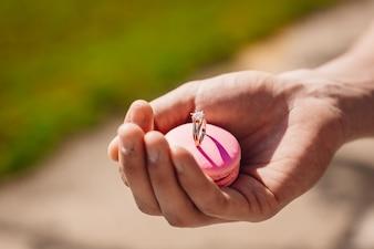 Homme tient un macaron rose avec une bague de mariage
