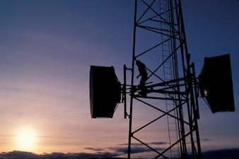 Homme travaillant sur la tour de communication