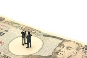 Hommes d'affaires miniatures secouer les mains debout sur les billets japonais