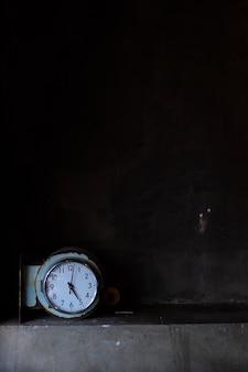 Horloge en métal de forme arrondie avec fond en béton noir