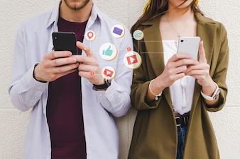 Icônes de notification mobile entre homme et femme à l'aide de téléphone portable