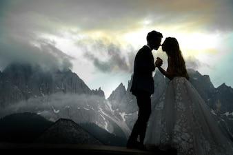 Image floue de baiser couple de mariage debout devant le magnifique paysage de montagne