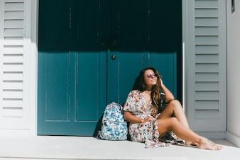 Jeune belle fille posant dans la rue dans une robe avec un sac à dos
