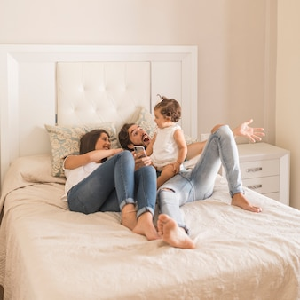 Jeune couple avec bébé sur lit