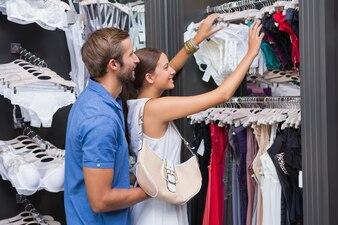 Jeune couple souriant heureux en regardant les vêtements