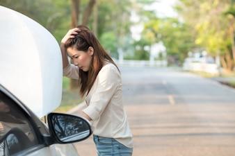 Jeune femme asiatique en regardant sa voiture en panne