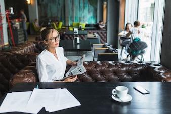 Jeune femme d'affaires avec un journal assis dans un café