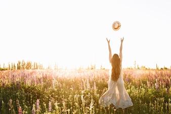 Jeune femme jeter chapeau de paille dans le champ de la fleur sur le coucher du soleil