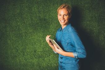 Jeune femme posant avec tablette par mur vert
